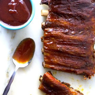 Spicy Asian BBQ Ribs | These oven baked Spicy Asian BBQ Ribs are smothered in a spicy sweet Asian inspired sauce that will have you licking your fingers and reaching for more. | Pack Momma | https://www.awickedwhisk.com