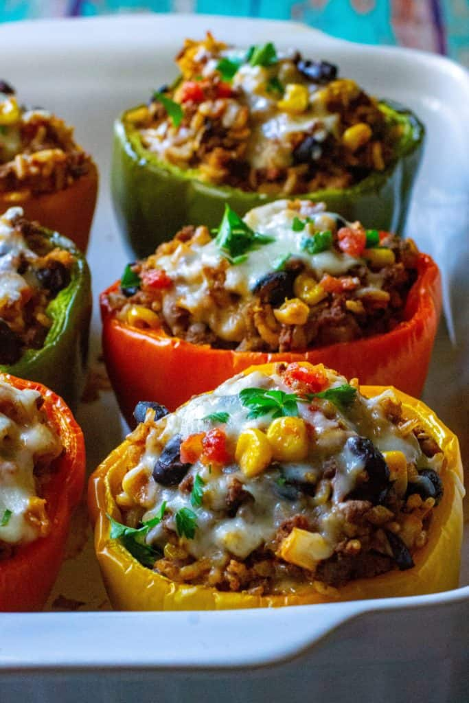 Mexican Stuffed Peppers are made by stuffing colorful bell peppers with ground beef, rice, cheese and all of your favorite Mexican-inspired flavors. The perfect easy weeknight meal, these Mexican Stuffed Peppers are healthy, delicious and a new twist on classic stuffed peppers. | A Wicked Whisk