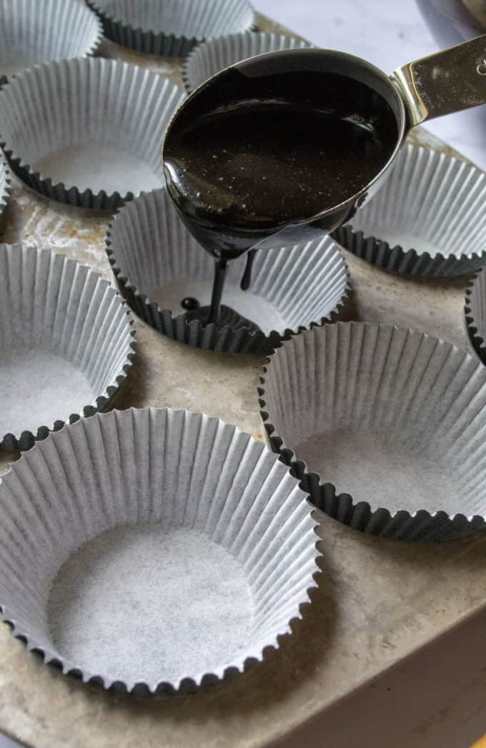 pouring cupcake batter into cupcake tin