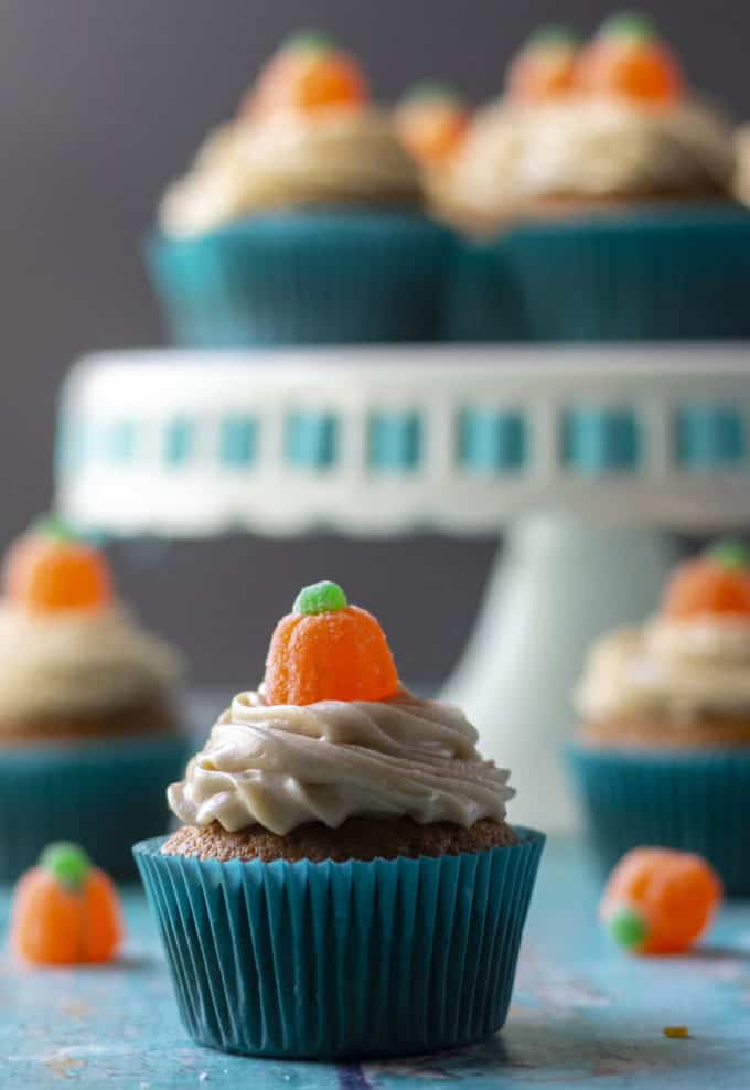frosted pumpkin cupcake in a blue wrapper