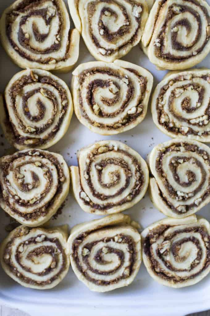 cinnamon buns cut into slices and uncooked in a baking pan