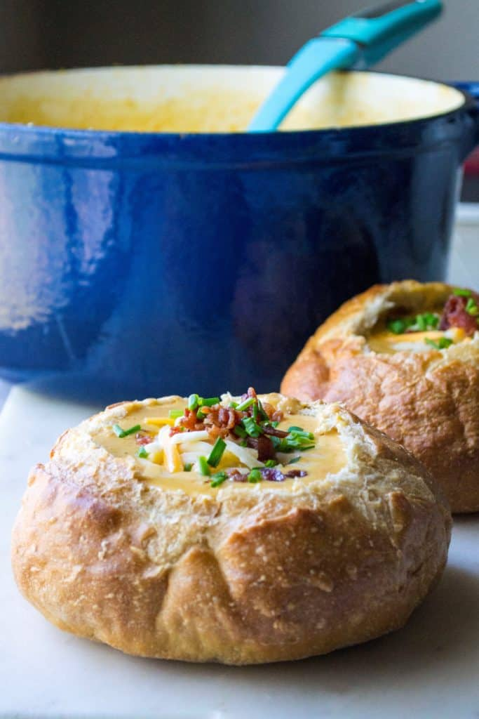 Beer Cheese Soup in a bread bowl with big blue soup pot in back ground