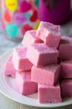 Pink White Chocolate Fudge stacked on a plate with a bite missing