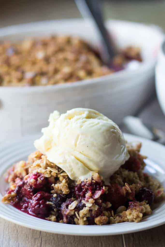 Triple Berry Crisp topped with vanilla ice cream on a white plate
