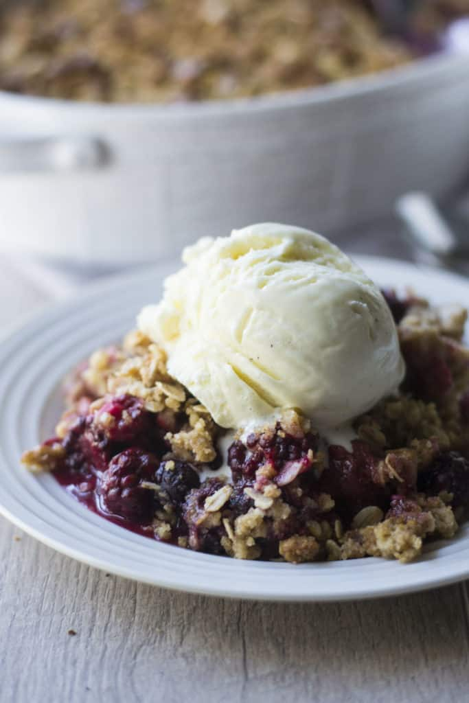 Triple Berry Crisp topped with vanilla ice cream close up