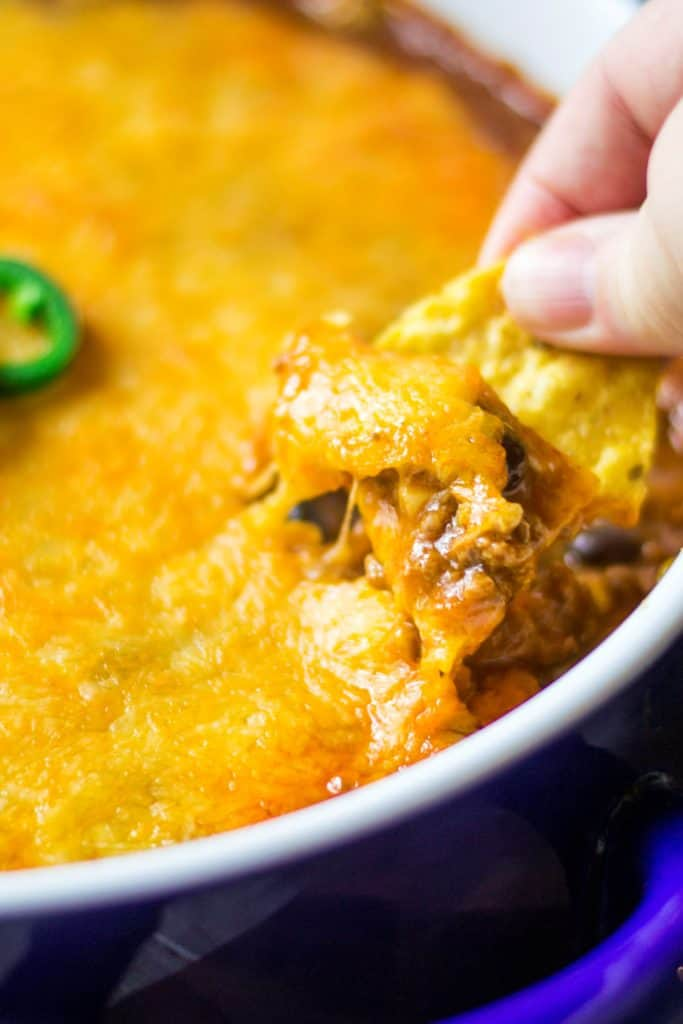 Beef Enchilada Dip is cheesy, spicy, packed with all of your favorite Mexican flavors and is completely MIND BLOWING! Kick up your tailgating and game day parties with this ultimate Beef Enchilada Dip to cheer on your teams on to victory.