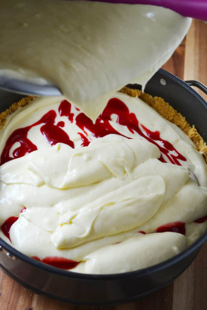 White Chocolate Raspberry Cheesecake batter pouring on raspberry sauce
