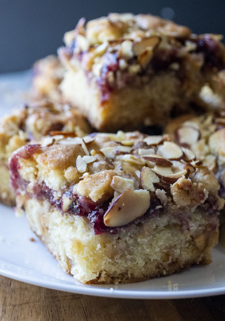 Raspberry Almond Crumble Bars are sweet, tart and packed with raspberry fruit flavor! These easy raspberry layers bars are made with a buttery crust, white chocolate chips, thick raspberry filling and a crunchy layer of almond crumble. The perfect summer dessert everyone will love!