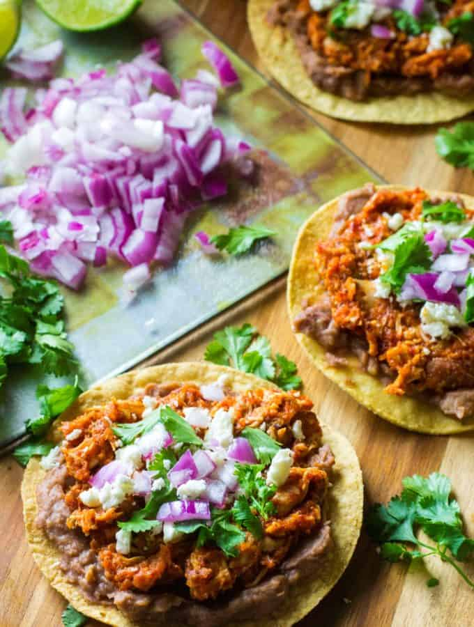 Chicken Tinga Tostadas are the perfect easy dinner idea to serve up any night of the week.  Made with rotisserie chicken, chipotle peppers and a few staple pantry items, these Chicken Tinga Tostadas are ready in under 30 minutes and are the ultimate healthy comfort food.