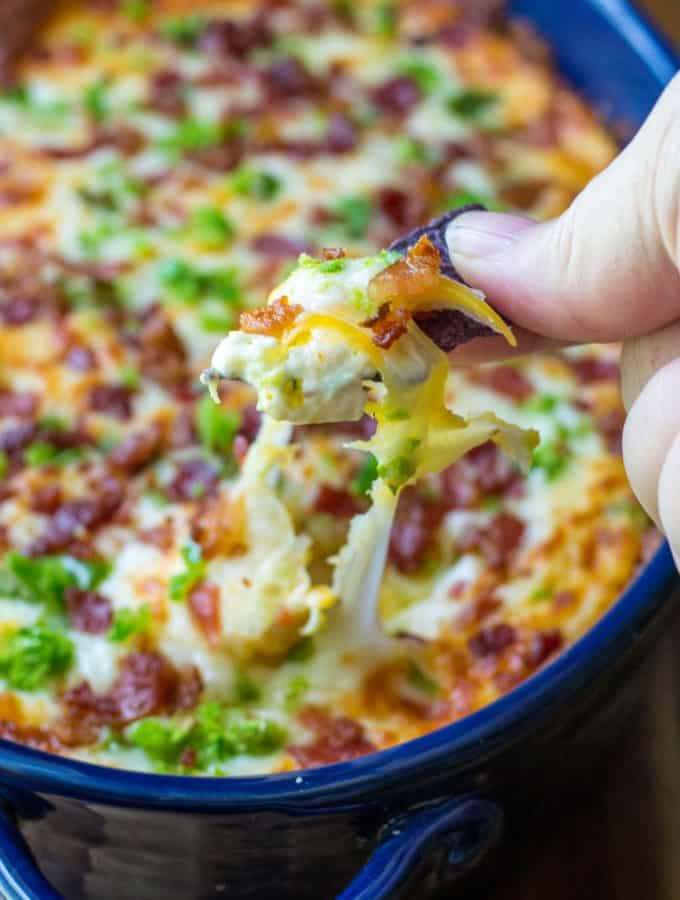 Cheesy Bacon Jalapeno Dip is warm, spicy and loaded with your favorite jalapeno popper flavors.  Easy to make and always a favorite cheesy appetizer, this Cheesy Bacon Jalapeno Dip is the perfect jalapeno dip to feed a crowd.