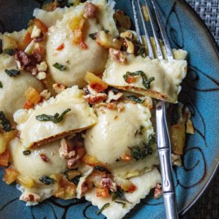 Pumpkin Ravioli in Apple Sage Butter Sauce are easy homemade pumpkin ravoili simmered in a rich sage butter and topped with apples and walnuts. Perfect fall comfort food!