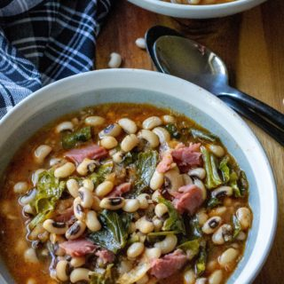 Slow Cooker Black Eyed Peas and Collard Greens is the perfect Southern comfort food to celebrate New Year's Day or ANY day! Made with a leftover ham bone and simmered in a rich tasty broth, these Slow Cooker Black Eyed Peas and Collard Greens are a delicious addition to your New Year's Day menu.