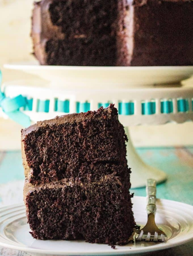 This dark, moist homemade chocolate cake recipe is made from scratch and the BEST chocolate cake recipe you will ever taste! Super easy to make and served up with homemade chocolate buttercream frosting, this Homemade Chocolate Cake is the best chocolate cake you will ever eat.. and you won't believe the secret ingredient that makes all the difrence!