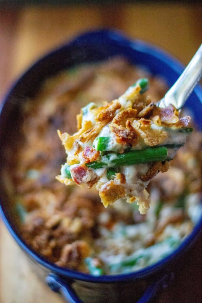 Green Bean Casserole with Bacon is everyone's favorite classic holiday side dish kicked up with tons of mouthwatering flavor. Made with fresh green beans, crispy bacon, topped with French fried onions and melted cheese and no condensed soup, this Green Bean Casserole with Bacon is the perfect easy side dish any night of the week. | A Wicked Whisk