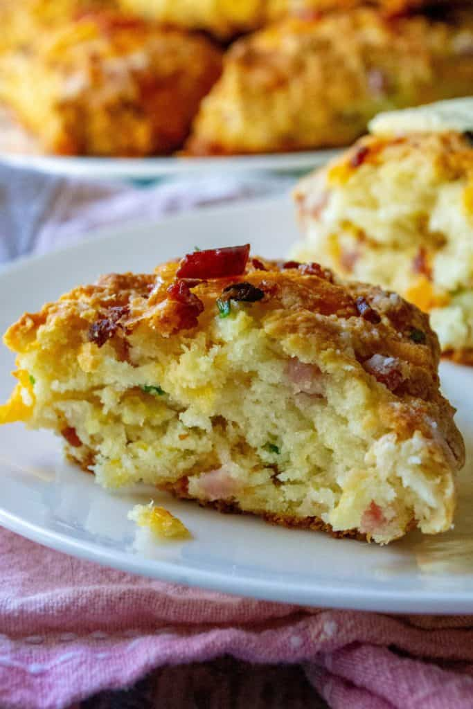 Ham and Cheese Scones are the perfect savory scones you have been looking for! Made with tons of cheddar cheese, crispy bacon, tender ham and chopped chives, these Ham and Cheese Scones are the perfect easy brunch idea any day of the week. | A Wicked Whisk