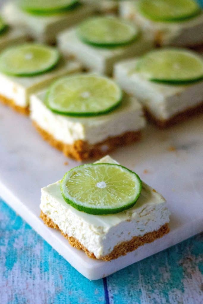 Key Lime Cheesecake Bars are creamy, low sugar and taste just like your favorite key lime pie cheesecake! Made with greek yogurt, fresh key limes and cream cheese, these Key Lime Cheesecake Bars are the perfect easy summer desserts. | A Wicked Whisk