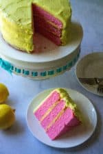 Pink Lemonade Cake is moist, tangy and the perfect summertime treat! Made from scratch with no frozen concentrate, this Pink Lemonade Cake is covered in lemon buttercream frosting and celebrates your favorite summertime drink with its bright pink cake color. | A Wicked Whisk