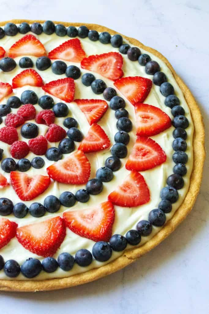 Red White and Blue Fruit Pizza is an easy fruit pizza that tastes amazing and will be your favorite Fourth of July dessert. Made with a Pillsbury sugar cookie crust, fresh fruit, powdered sugar, lime and cream cheese, this Red White and Blue Fruit Pizza is the perfect patriotic dessert to show off your Ameican pride! | A Wicked Whisk