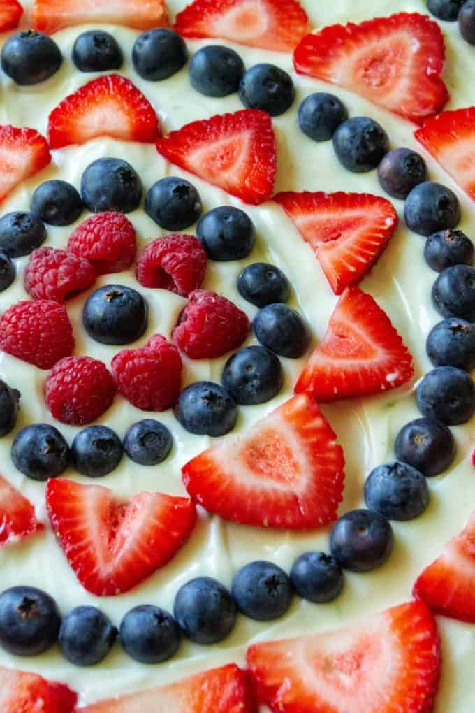 Red White and Blue Fruit Pizza is an easy fruit pizza that tastes amazing and will be your favorite Fourth of July dessert. Made with a Pillsbury sugar cookie crust, fresh fruit, powdered sugar, lime and cream cheese, this Red White and Blue Fruit Pizza is the perfect patriotic dessert to show off your Ameican pride!