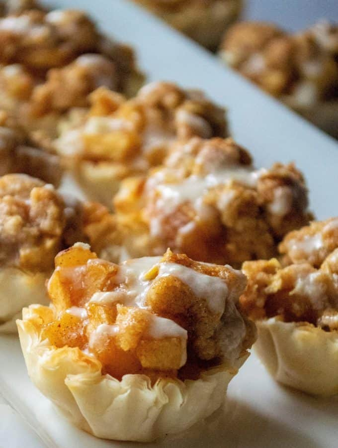 Dutch Apple Pie Bites have all of the flavor of homemade apple pie with none of the hassel. Made using pre-made phyllo cups, a traditional apple pie filling and a crumbly topping, these Dutch Dutch Apple Pie Bitesare easy to make and impossible to resist!