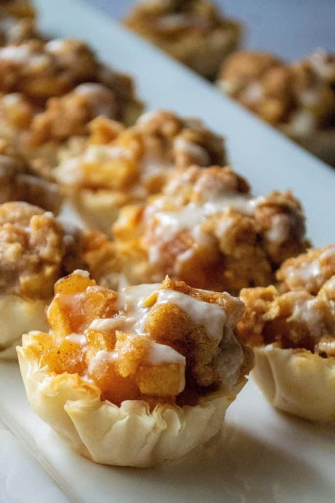 Dutch Apple Pie Bites have all of the flavor of homemade apple pie with none of the hassel.  Made using pre-made phyllo cups, a traditional apple pie filling and a crumbly topping, these Dutch Dutch Apple Pie Bites are easy to make and impossible to resist!