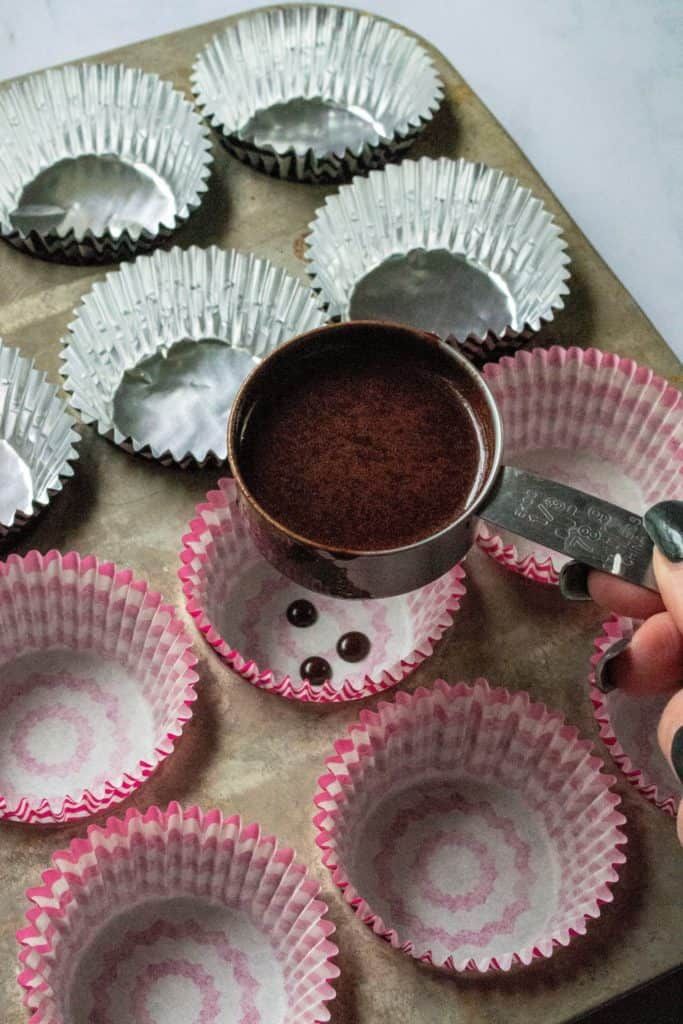 pouring cupcake batter into liners