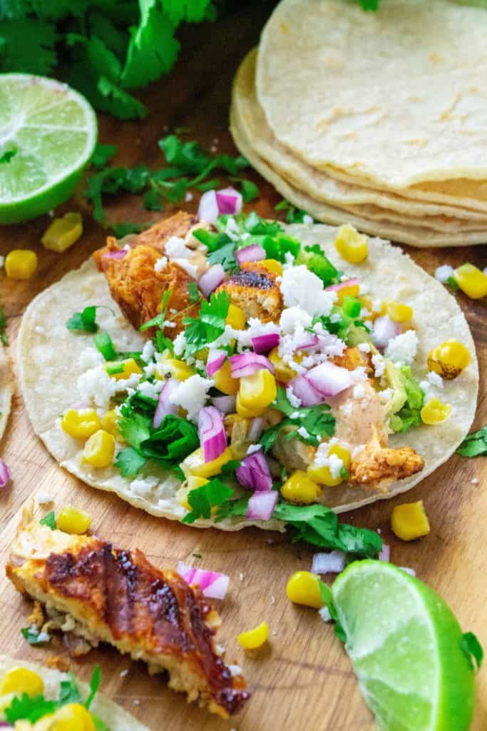 Mexican Street Corn Chicken Tacos bring together your love of Mexcian steet food elote and spicy chicken tacos. Made with fresh roasted corn, cilantro, lime, seasoned chicken and a creamy chipotle sauce, these Mexican Street Corn Chicken Tacos will have you begging for more!