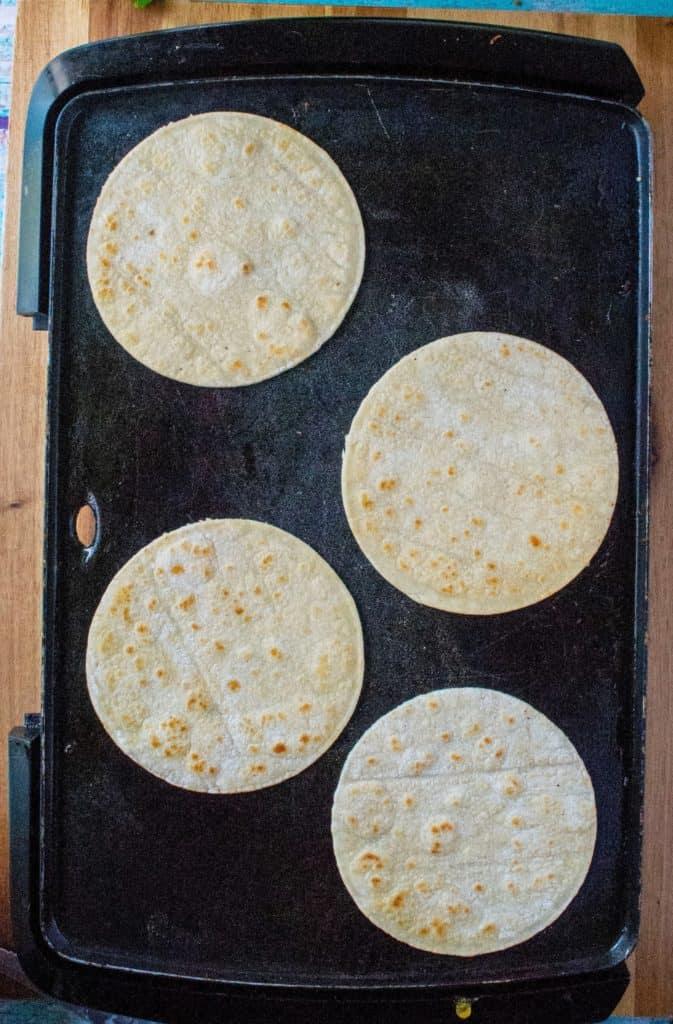 corn tortillas on a griddle