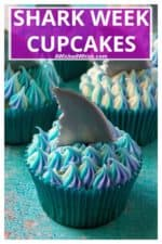 Shark Week Cupcakes are easy to make, fun to eat and the perfect sweet treat to sink your teeth into. Homemade orange cupcakes filled with a bite of rasberry orange sauce, these Shark Week Cupcakes are great for viewing parties, days at the beach or watching your favorite shark show on TV. | A Wicked Whisk #sharkweekcupcakes #sharkweekfood #sharkweekparty #sharkweekfoodideas #sharkweekfoodrecipes #sharkweekdesserts #sharkattackcupcakes