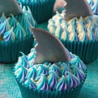 Shark Week Cupcakes are easy to make, fun to eat and the perfect sweet treat to sink your teeth into. Homemade orange cupcakes filled with a bite of rasberry orange sauce, these Shark Week Cupcakes are great for viewing parties, days at the beach or watching your favorite shark show on TV.