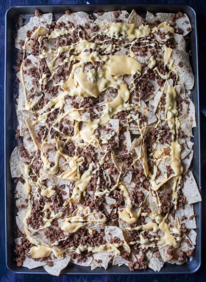 tortilla chips on a sheet pan with seasoned beef and cheese