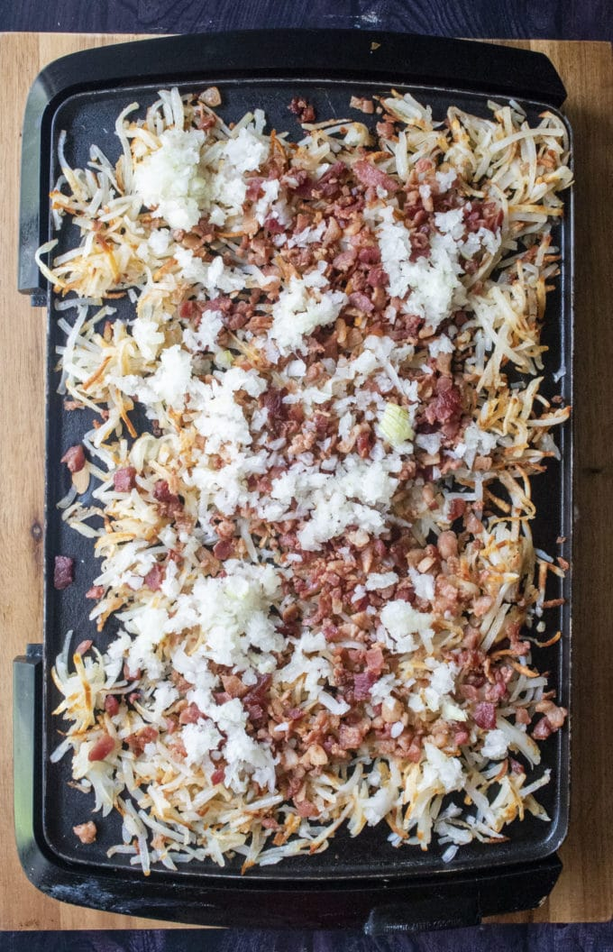 hashbrowns with bacon and onions on a griddle